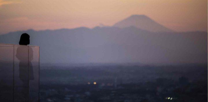 Una mujer mira la puesta de sol desde la plataforma de un observatorio con el monte Fuji de fondo, la montaña más alta de Japón con 3.776 metros (12.388 pies), en Tokio.
