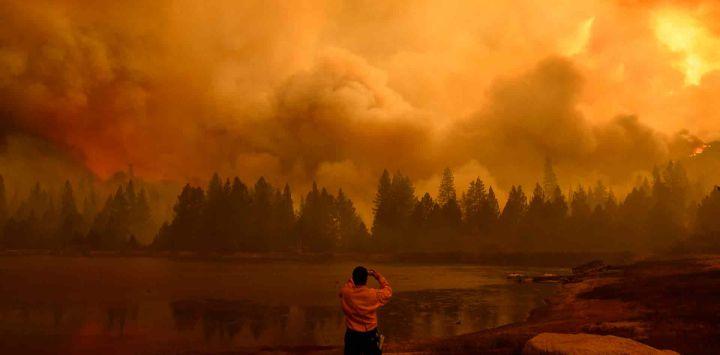 Un oficial de información pública toma fotografías mientras las llamas y el humo se elevan en el aire mientras el fuego arde durante el WindyFire en el Bosque Nacional Sequoia cerca de Johnsondale, California.