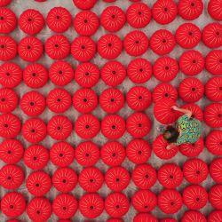 Esta foto aérea muestra a un trabajador que produce linternas rojas antes del Día Nacional de China en Danzhai, en la provincia suroeste de Guizhou. | Foto:AFP