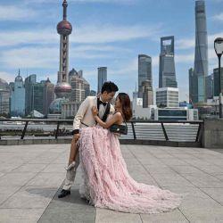 Una pareja posa durante una sesión de fotos previa a la boda en el paseo marítimo del Bund a lo largo del río Huangpu en Shanghai.  | Foto:AFP