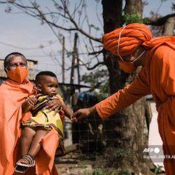SwamiMaitri y SwamiVedanandaSaraswati del Movimiento AryaSamaj de Sudáfrica interactúan con AsandeMadima de 1 año vestida con atuendo tradicional zulú durante el lanzamiento de la Campaña del Día Nacional de la Vacuna VaxuMzansi en el Asentamiento de Gandhi Phoenix en el municipio de Bhambayi.  | Foto:AFP