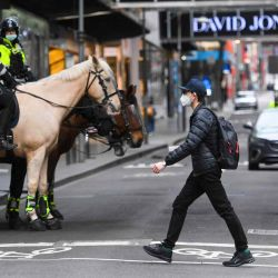 Los residentes pasan junto a agentes de policía que patrullan por el centro de la ciudad mientras intentan evitar las protestas de los trabajadores de la construcción y los manifestantes contra las regulaciones de Covid-19, en Melbourne.    Foto:AFP