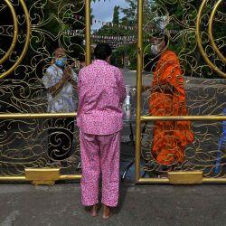 Una mujer ofrece comida y limosna a un monje budista mientras reza durante el festival Pchum Ben (Festival de la Muerte) fuera de una pagoda en Phnom Penh.   Foto:AFP