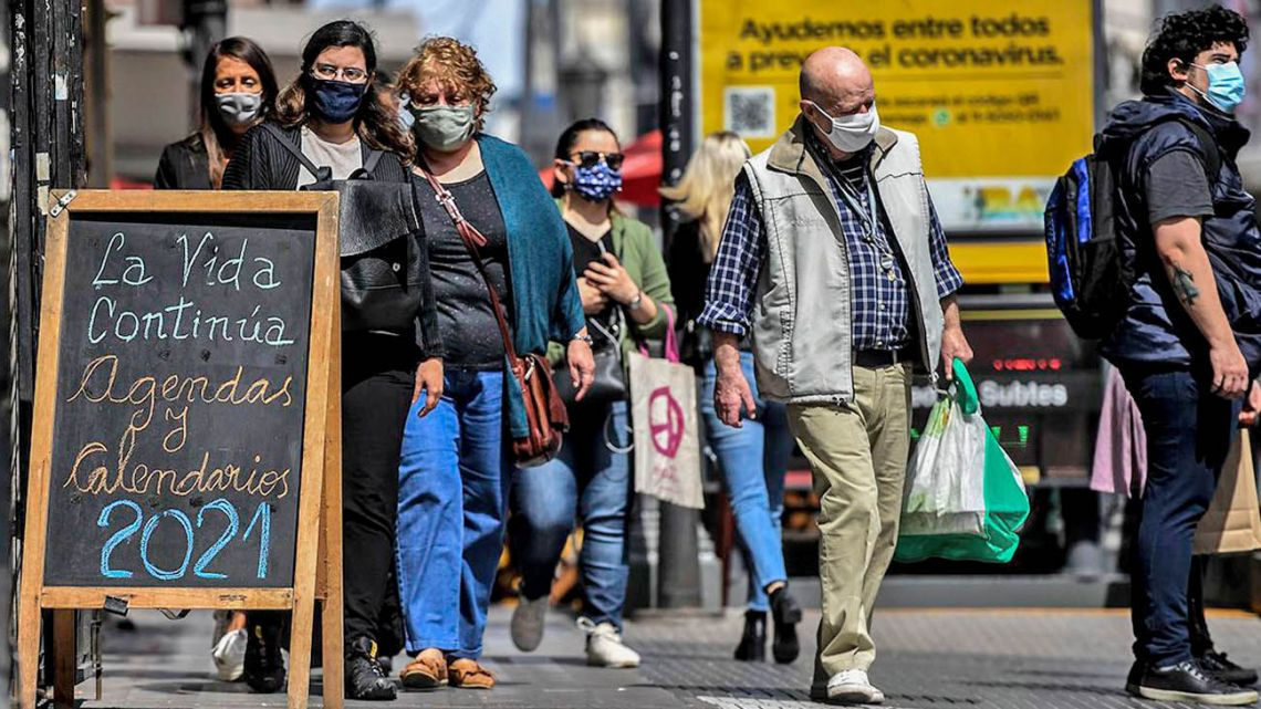 Porteños walk wearing facemasks on the streets of Buenos Aires.