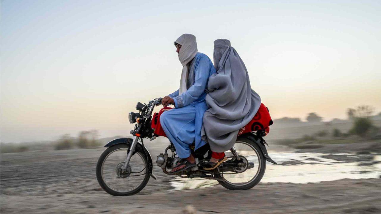Un hombre y una mujer viajan en motocicleta en Kandahar.  | Foto:AFP