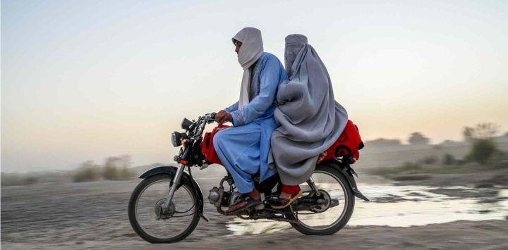 Un hombre y una mujer viajan en motocicleta en Kandahar.