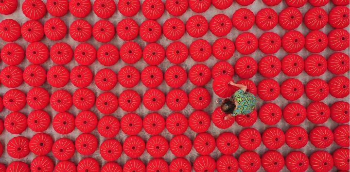 Esta foto aérea muestra a un trabajador que produce linternas rojas antes del Día Nacional de China en Danzhai, en la provincia suroeste de Guizhou.