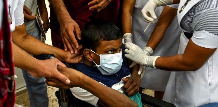 Un trabajador de la salud vacuna a un niño con una dosis de la vacuna Pfizer-BioNTech contra el coronavirus Covid-19 en un hospital infantil en Colombo.