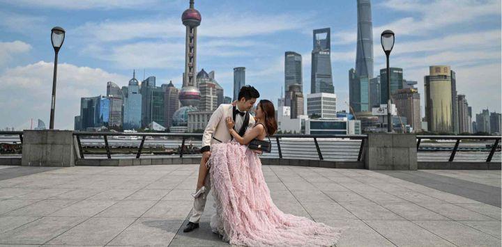 Una pareja posa durante una sesión de fotos previa a la boda en el paseo marítimo del Bund a lo largo del río Huangpu en Shanghai.