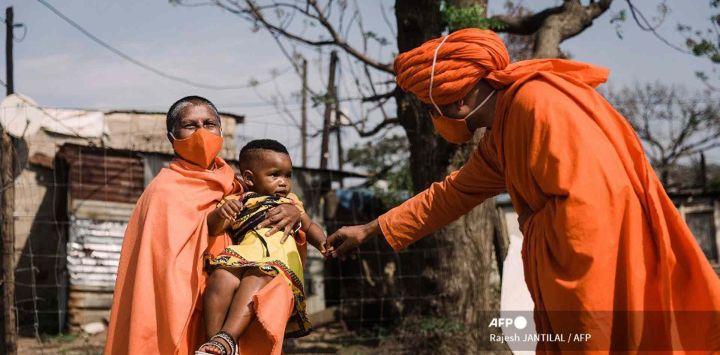 SwamiMaitri y SwamiVedanandaSaraswati del Movimiento AryaSamaj de Sudáfrica interactúan con AsandeMadima de 1 año vestida con atuendo tradicional zulú durante el lanzamiento de la Campaña del Día Nacional de la Vacuna VaxuMzansi en el Asentamiento de Gandhi Phoenix en el municipio de Bhambayi.