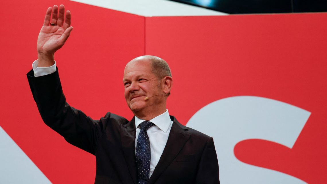 German Finance Minister, Vice-Chancellor and the Social Democrats (SPD) candidate for Chancellor Olaf Scholz waves at the Social Democrats (SPD) headquarters after the estimates were broadcast on TV, in Berlin on September 26, 2021 after the German general elections.
