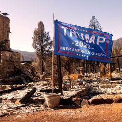Una bandera de Donald Trump ondea al viento frente a una residencia quemada en Greenville, California. - El incendio de Dixie se mantiene en un 94% de contención después de quemar 5 condados y más de 1.000 casas. | Foto:Josh Edelson / AFP