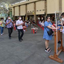 La gente hace cola para recibir una ostia de comunión detrás de una pantalla mientras se observan las medidas de prevención contra el coronavirus Covid-19, en una catedral en Yakarta. | Foto:Adek Berry / AFP