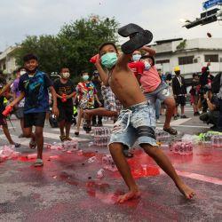 Jóvenes manifestantes antigubernamentales lanzan botellas de pintura roja a la policía durante una manifestación en Bangkok, mientras los activistas piden la dimisión del primer ministro de Tailandia, Prayut Chan-O-Cha, por la gestión gubernamental de la crisis del coronavirus Covid-19. | Foto:Jack Taylor / AFP
