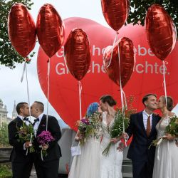 Unas parejas posan durante un evento fotográfico durante la jornada del referéndum nacional sobre el matrimonio entre personas del mismo sexo, en Berna, capital de Suiza. | Foto:Fabrice Coffrini / AFP