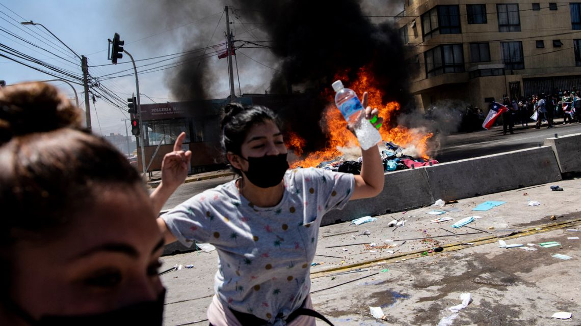 A makesifht camp of Venezuelan migrants burns after after being set on fire by demonstrators during a protest march against illegal migration in Iquique, Chile on September 25, 2021.