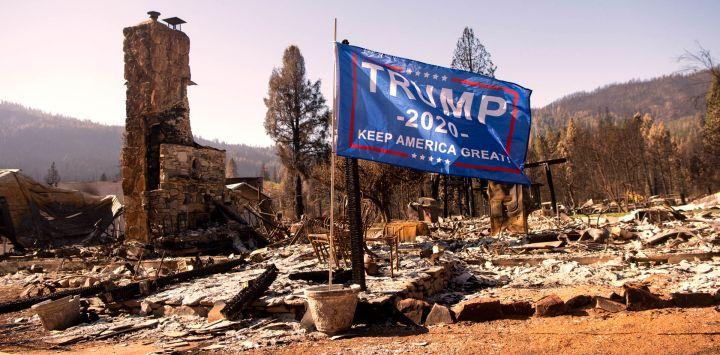 Una bandera de Donald Trump ondea al viento frente a una residencia quemada en Greenville, California. - El incendio de Dixie se mantiene en un 94% de contención después de quemar 5 condados y más de 1.000 casas.