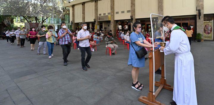 La gente hace cola para recibir una ostia de comunión detrás de una pantalla mientras se observan las medidas de prevención contra el coronavirus Covid-19, en una catedral en Yakarta.