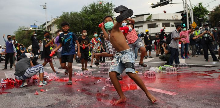 Jóvenes manifestantes antigubernamentales lanzan botellas de pintura roja a la policía durante una manifestación en Bangkok, mientras los activistas piden la dimisión del primer ministro de Tailandia, Prayut Chan-O-Cha, por la gestión gubernamental de la crisis del coronavirus Covid-19.