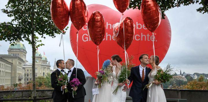Unas parejas posan durante un evento fotográfico durante la jornada del referéndum nacional sobre el matrimonio entre personas del mismo sexo, en Berna, capital de Suiza.