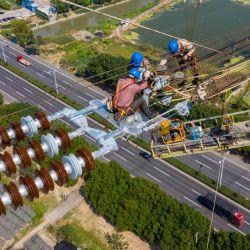 Esta foto muestra a empleados trabajando en una línea de transmisión de corriente continua de alta tensión en Wuxi, en la provincia oriental china de Jiangsu.   Foto:STR / AFP