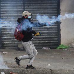 Un hombre lanza una lata de gas lacrimógeno durante un enfrentamiento entre policías y cocaleros de los Yungas que pretenden retomar la sede de la Asociación Departamental de Productores de Coca, en La Paz, Bolivia.   Foto:Xinhua/Mateo Romay