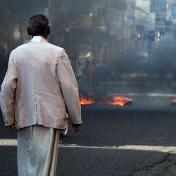 Un hombre yemení mira durante las protestas que reclaman la eliminación del gobierno de coalición respaldado por Arabia Saudí y el deterioro de las condiciones económicas y de vida, en la tercera ciudad de Yemen, Taez. | Foto:Ahmad AL-Basha / AFP