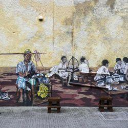 Un hombre sentado frente a un mural en Kuala Lumpur. | Foto:Mohd Rasfan / AFP