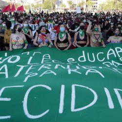 Manifestantes sostienen una bandera verde durante una marcha de celebración después de que la cámara baja diera un paso hacia la despenalización del aborto, en Santiago, Chile. | Foto:Pablo Vera / AFP