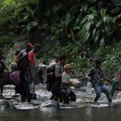 Migrantes haitianos atraviesan la selva del Tapón del Darién, cerca de Acandí, departamento del Chocó, Colombia, en dirección a Panamá, en su intento de llegar a Estados Unidos. | Foto:Raúl Arboleda / AFP
