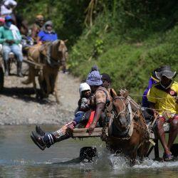 Migrantes haitianos cruzan el río en carros tirados por caballos antes de dirigirse a la frontera con Panamá en Acandí, Colombia.   Foto:Raúl Arboleda / AFP