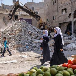 Unas mujeres pasan por delante de un puesto de verduras, mientras unos trabajadores limpian los escombros de un edificio destruido por los bombardeos israelíes el pasado mayo, en Rafah, en el sur de la Franja de Gaza. | Foto:Said Khatib / AFP