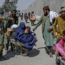 Personas con sus pertenencias se apresuran a pasar a Pakistán desde la frontera con Afganistán en Spin Boldak. | Foto:BULENT KILIC / AFP