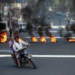 Unos yemeníes pasan junto a unos neumáticos ardiendo durante las protestas que reclaman la retirada del gobierno de coalición respaldado por Arabia Saudí y el deterioro de las condiciones económicas y de vida, en la tercera ciudad de Yemen, Taez. | Foto:Ahmad AL-Basha / AFP