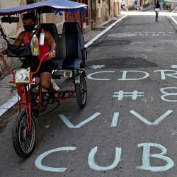 Un hombre circula en un triciclo sobre un cartel escrito en el pavimento que dice  | Foto:Yamil Lage / AFP