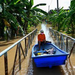 Un residente dirige su bote sobre un puente peatonal a través de un barrio inundado en la provincia central tailandesa de Ayutthaya, ya que la tormenta tropical Dianmu causó inundaciones en 30 provincias del país. | Foto:Lillian Suwanrumpha / AFP