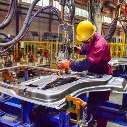 Un trabajador ensambla parte de un vehículo en una fábrica de Qingzhou, en la provincia oriental china de Shandong.   Foto:STR / AFP