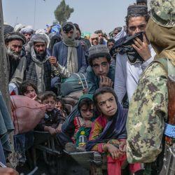 Unas personas se paran cuando miembros talibanes los detienen mientras se apresuran a pasar a Pakistán desde la frontera con Afganistán en Spin Boldak. | Foto:Bulent Kilic / AFP