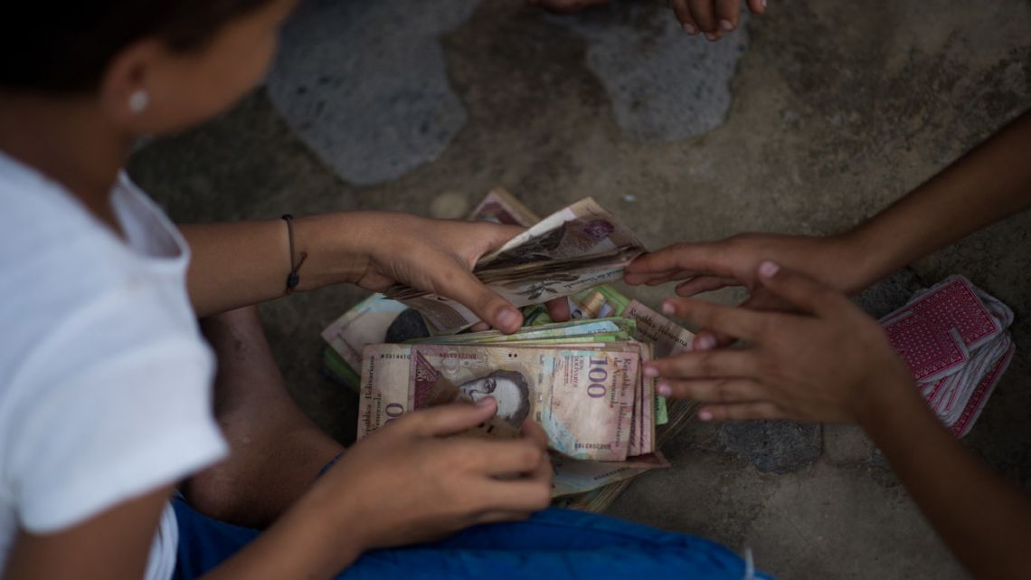 Children play cards and bet with unused Venezuelan bolivar bills on a street of Puerto Concha town, Zulia state, Venezuela, on September 9, 2021.
