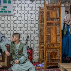 Un hombre acusado de robo se sienta junto a miembros talibanes mientras está detenido en una estación de policía en Kabul. | Foto:BULENT KILIC / AFP