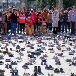 La gente se coloca alrededor de los zapatos que honran a todos los niños indígenas desaparecidos durante el primer Día Nacional de la Verdad y la Reconciliación, en la Colina del Parlamento en Ottawa. | Foto:Lars Hagberg / AFP