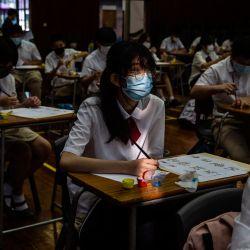 Estudiantes participan en un ejercicio de caligrafía en una escuela del distrito de Yuen Long, en Hong Kong. | Foto:Isaac Lawrence / AFP