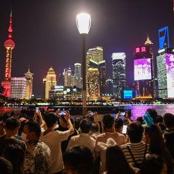 La gente toma fotos del horizonte de Shanghái desde el Bund a lo largo del río Huangpu durante el día nacional de China que marca el 72º aniversario del establecimiento de la República Popular China y la fiesta de la  | Foto:Hector Retamal / AFP