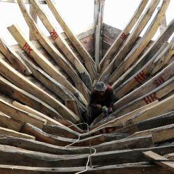 Un trabajador construye un barco de pesca de madera en un astillero en Lhokseumawe, Aceh. | Foto:Azwar Ipank / AFP