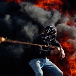 Las llamas surgen de los neumáticos quemados mientras un manifestante palestino lanza piedras a las fuerzas de seguridad israelíes durante los enfrentamientos con ellas tras una manifestación contra los asentamientos en el pueblo cisjordano de Beita. | Foto:JAAFAR ASHTIYEH / AFP