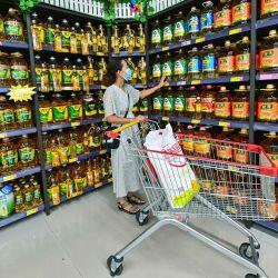 Una clienta compra aceite comestible en un supermercado, en Qingzhou, en la provincia de Shandong, en el este de China.   Foto:Xinhua/Wang Jilin
