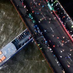 Los competidores corren sobre el Tower Bridge mientras un barco pasa por debajo, mientras compiten en el Maratón de Londres 2021 en el centro de Londres.   Foto:Tolga Akmen / AFP