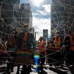 """Unas personas sostienen un atrapasueños gigante durante la marcha """"Every Child Matters"""" para conmemorar el primer Día Nacional de la Verdad y la Reconciliación en Montreal, Canadá.   Foto:Andrej Ivanov / AFP"""