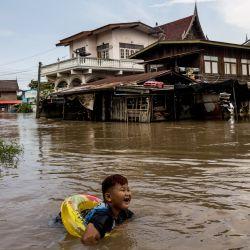 Un niño lleva un flotador mientras nada en las aguas de la inundación en un barrio de Ayutthaya, después de que la tormenta tropical Dianmu provocara inundaciones en 31 provincias del país.   Foto:Jack Taylor / AFP