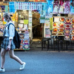 Una mujer pasa por delante de un restaurante en Tokio.   Foto:Charly Triballeau / AFP